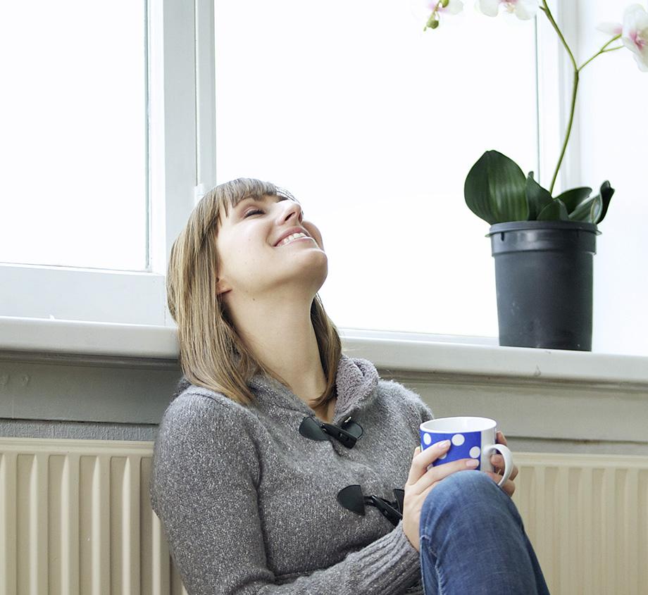 Frau mit einer Tasse vor der Heizung