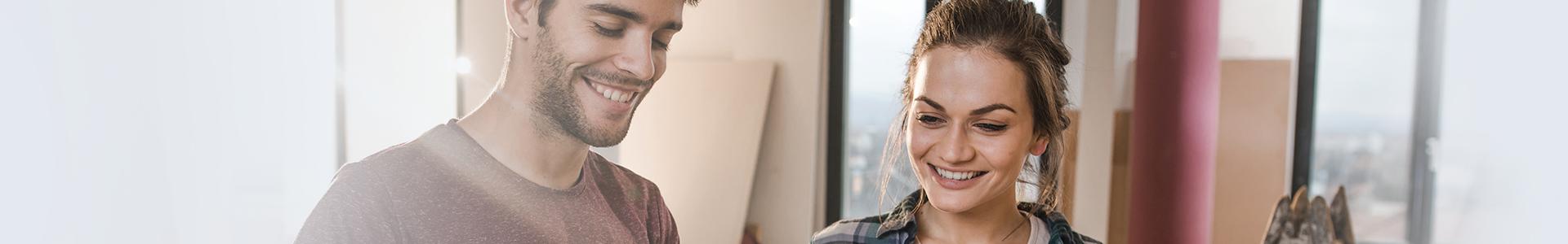 Junge glückliche Paar Baupläne selbst auf Baustelle in ihrer Wohnung zu prüfen