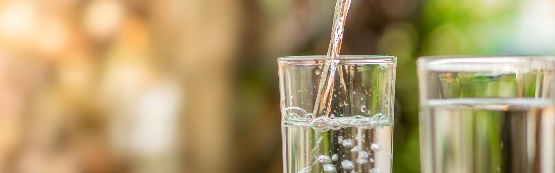 Zwei Wassergläser werden mit Wasser gefüllt