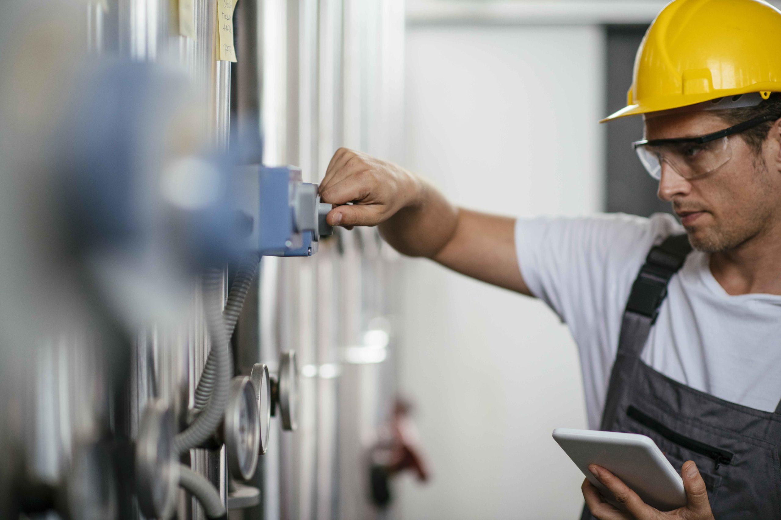 Mann mit Tablet bei Erdgas verarbeitenden Anlage